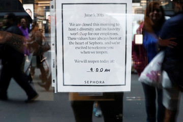 People wait outside a LVMH's Sephora beauty chain sign is posted on the door stating it is closed in the morning to conduct diversity training for employees in New York City