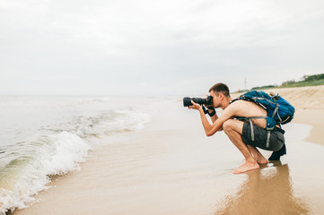 Man with photo camera taking picture of sea. Man photographer siting on beach and taking photo of nature.