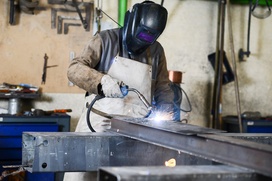 handsome man workshop welding iron spark fire hot steel with power GMAW welder and protective gear