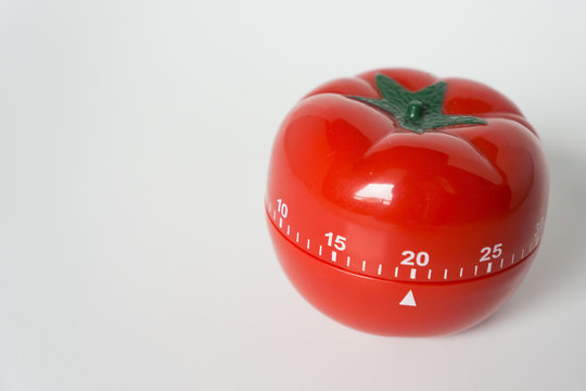 Close up view of mechanical tomato shaped kitchen clock timer for cooking & studying. Used for pomodoro technique for time and productivity management. Isolated on white background, set at 20 minutes.