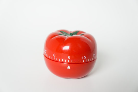 Close up view of mechanical tomato shaped kitchen clock timer for cooking & studying. Used for pomodoro technique for time and productivity management. Isolated on white background, set at 5 minutes.