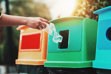 people hand holding garbage bottle plastic putting into recycle bin for cleaning