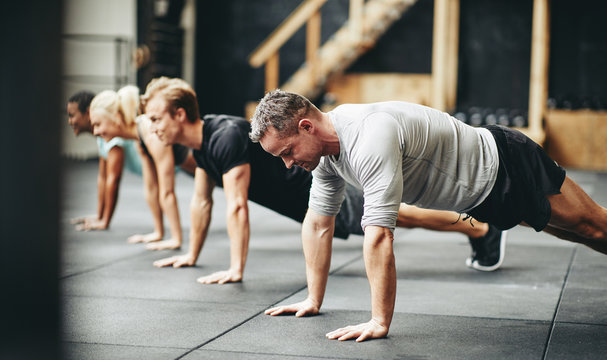 Fit people doing pushups together during a gym exercise class