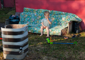 In early spring, in the village, a little blond boy sits on the street in the yard of his house on an old sofa, covered with a floral blanket, on his face a variety of emotions