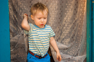 In early spring, in the village, a small blond boy of three years old, chumazenky, comes out of his village house, whose door is covered with insect tulle