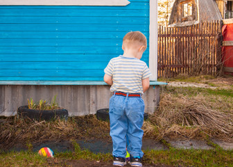 In early spring, in the village, a little blond boy of three years old, stands with his back to the audience against the blue wall of his village house