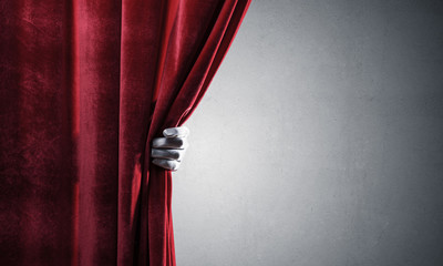 Concrete wall behind drapery curtain and hand opening it