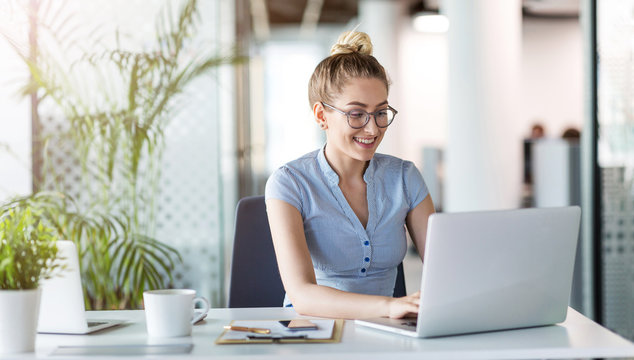 Young business woman working on laptop in office