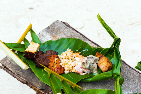 Fried meat with rice on a banana leaf, Bora Bora, French Polynesia. With selective focus.                    .