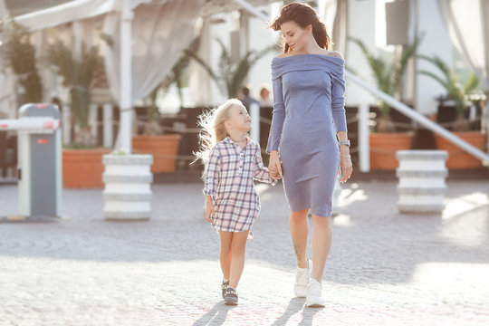 Mother and daughter outdoors in city. playing and having fun. Fashion happy mother and child daughter having fun together in the city.Mother with little charming daughter are joy in the city