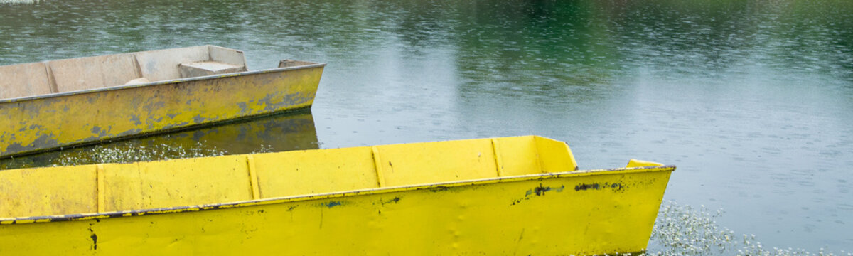 Relaxing view of small yellow fishing boat in the lake with wild flowers on the surface
