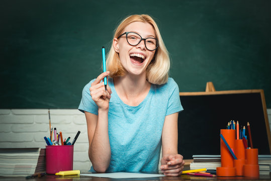 Young woman sitting at table doing assignments library. Young happy student. World teachers day. Happy casual girl student with over blackboard background.