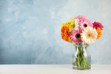 Bouquet of beautiful bright gerbera flowers in glass vase on table against color background. Space for text