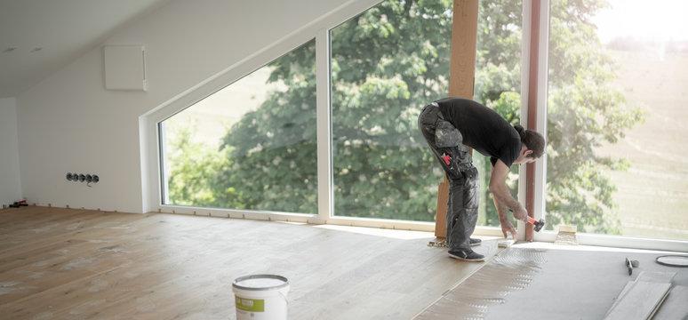 Handwerker legt Parkettboden und schlägt gerade die Holzdielen mit dem Schlagholz und dem Hammer aneinander