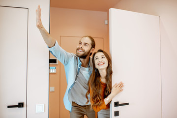 Portrait of a young couple looking out the door at the corridor of the new modern apartment. Concept of happy real estate owners