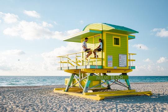 Miami south Beach, youn couple men and woman on the beach during sunrise. Miami beach Floarida