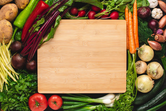 Empty Wood Cutting Board Mockup with Fresh Vegetables. Vegetarian Raw Food. Healthy Eating Concept with Copy Space.
