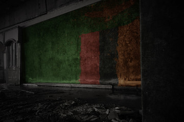 painted flag of zambia on the dirty old wall in an abandoned ruined house.