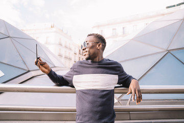 Spain, Madrid, young man taking selfie with smartphone