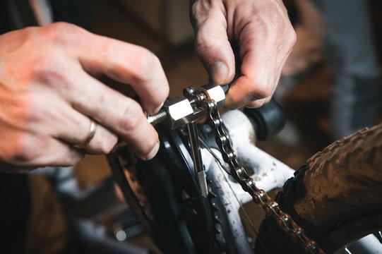 Bike service: mechanic serviceman repairman installing assembling or adjusting bicycle gear on wheel in workshop