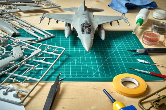 Top view on plastic model scale with accessories on  green pad on  wooden table