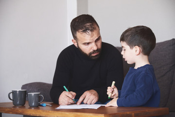 Adult bearded man helping little boy to draw picture while sitting at table at home together