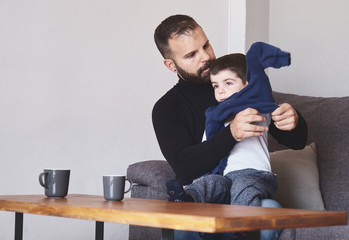 Adult bearded male putting on sweatshirt on little boy while sitting in armchair together