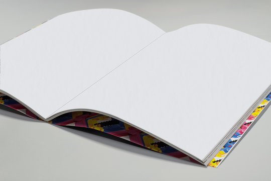 Opened empty notebook with white sheets and colorful funny cover on grey background