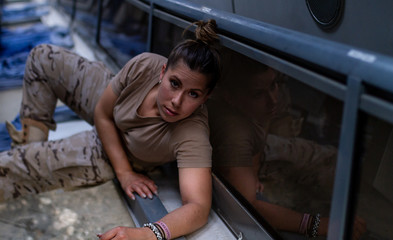 Female soldier looking at camera while lying on floor of contemporary military transport