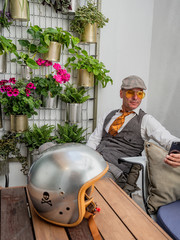 Pensive middle-aged hipster in elegant clothes sitting at wooden table with motorcycle helmet using smartphone