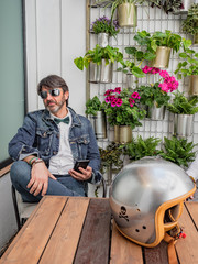 Pensive middle-aged hipster in elegant clothes and sunglasses sitting at wooden table with motorcycle helmet using smartphone