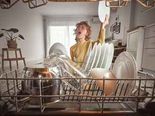 Little boy with wavy hair yawning while standing near open dishwasher in early morning in kitchen