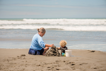 Grandmother and grandchild building a sandcastle together at a beach