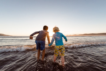 Two boys holding hands in water at the beach at sunset