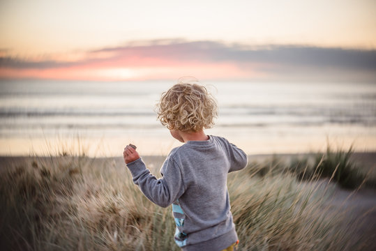 Boy with long curly hair running to the beach at sunrise