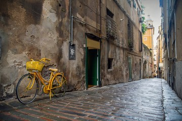 "Street view of an ancient narrow alley (""caruggio"" in Genoese) in the historic centre of Genoa with a yellow bicycle parked against a scraped wall and the pavement of stones and bricks, Liguria, Italy"