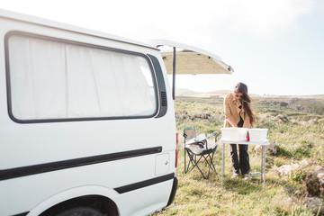 Full length view of woman preparing picnic outdoors by a camper van