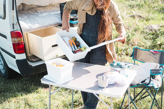 Close up of woman preparing picnic outdoors by a camper van