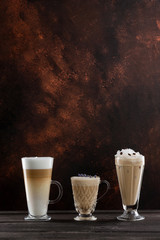 Three cups of coffee at wooden table background. Vertical image with free space.