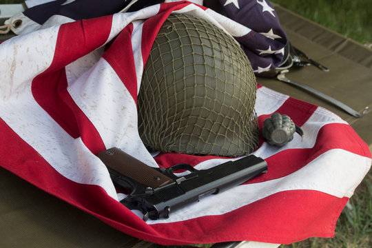 Soldier helmet, pistolt and grenade from the Second World War and the flag of the USA. Patriotism