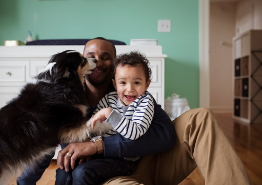 Dog licking man holding son while sitting against cabinet at home