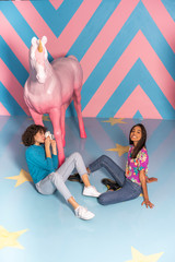 Young woman taking a picture of her friend at an indoor theme park with a unicorn figure