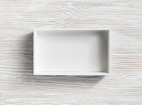 Blank white opened box on light wooden background. Flat lay.