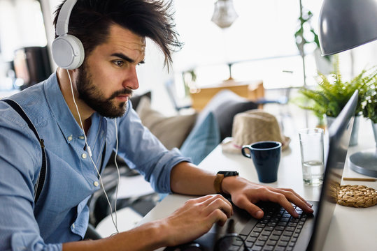 Young modern bearded man working with laptop computer indoors