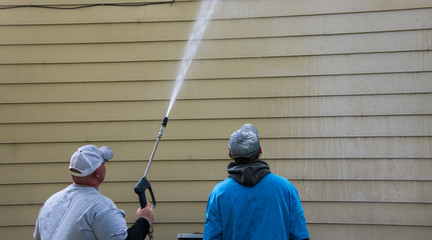 Two young men standing by the side of a yellow house. One is power washing the siding with a long nozzle.