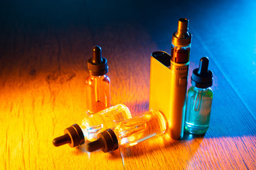 The vaping concept. E-cigs. Vaping set standing on a table in a multicolored light. Vapes and bottles with filling liquid. Electronic devices for smoking. Smoking gadgets.