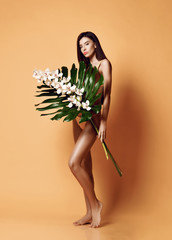 Portrait of young and beautiful woman with perfect smooth skin in tropical leaves. Concept of natural cosmetics and skincare
