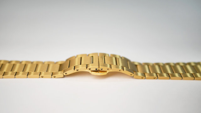 A shiny gold colored metal chain link wrist watch band laying flat on a white table.