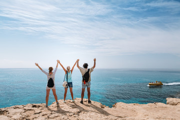 The company of friends of travelers stand on the edge of a cliff against the background of the sea. They raised their hands up. Cyprus.