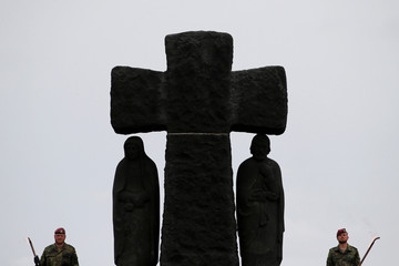 German soldiers stand next to a cross of La Cambe German war cemetery during a remembrance ceremony in La Cambe in Normandy